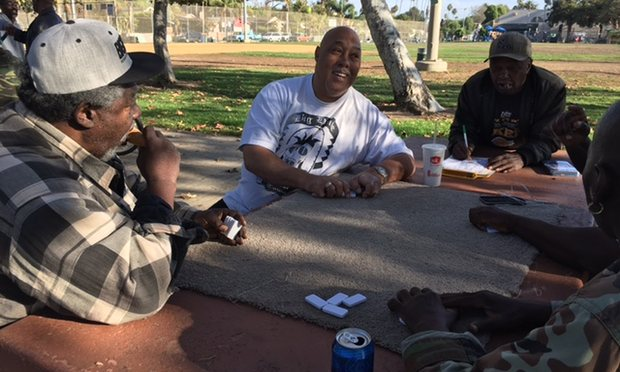 Donald Coulter, centre, playing dominos with friends in Oakwood park, Venice. Photograph: Rory Carroll